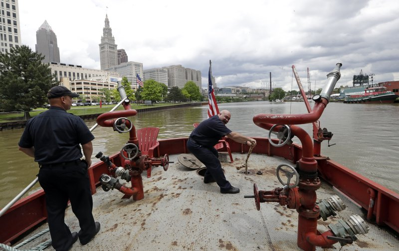 Firemen maintain the Anthony J. Celebrezze as it floats down the Cuyahoga River, Thursday, June 13, 2019, in Cleveland. The fire boat extinguished hot spots on a railroad bridge torched by burning fluids and debris on the Cuyahoga River in 1969. (AP Photo/Tony Dejak)