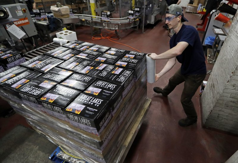 A worker shrink wraps cases of Burning River beer at The Great Lakes Brewing Company, Monday, June 17, 2019, in Cleveland. The