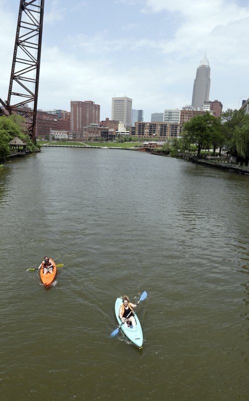 "Kylie Augustine, left, and Ashlie Prosky paddle in kayaks on the Cuyahoga River, Tuesday, May 28, 2019, in Cleveland. Fifty years after the Cuyahoga River's famous fire, a plucky new generation of Cleveland artists and entrepreneurs has turned the old jokes about the ""mistake on the lake"" into inspiration and forged the decades of embarrassment into a fiery brand of local pride. (AP Photo/Tony Dejak)"