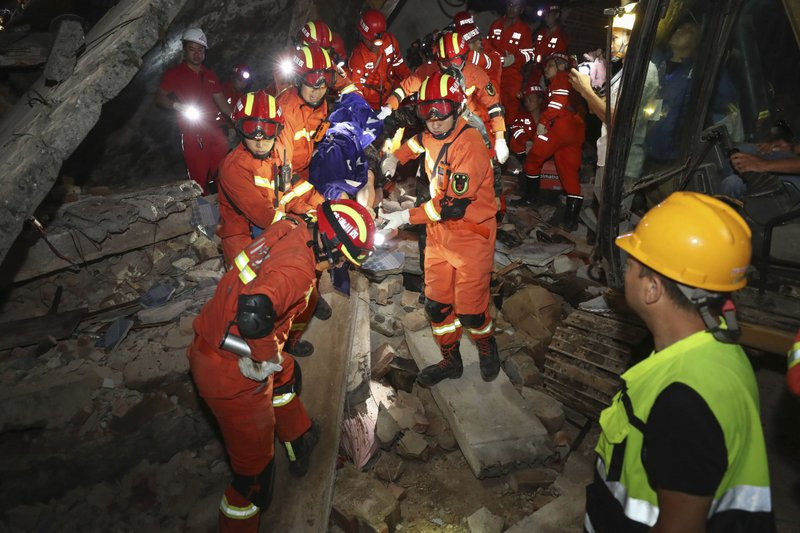 In this photo released by Xinhua News Agency, rescue workers carry out a person from a collapsed building following a strong earthquake at Putao village of Shuanghe town in Changning County of Yibin City, southwest China's Sichuan Province, Tuesday, June 18, 2019. (Zhuang Ge'er/Xinhua via AP)