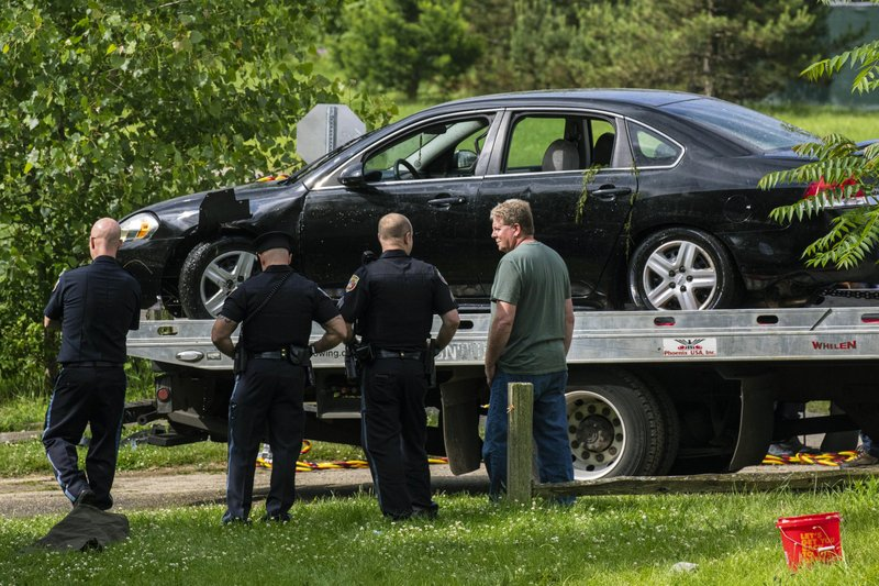 Police remove a black sedan from the Kalamazoo River near Verburg Park, Tuesday morning, June 18, 2019, after finding the bodies of a mother and child inside the submerged vehicle, in Kalamazoo, Mich. Police believe a second child, who is missing, may also have been inside the vehicle when it entered the water late Monday evening. (Joel Bissell/Kalamazoo Gazette via AP)