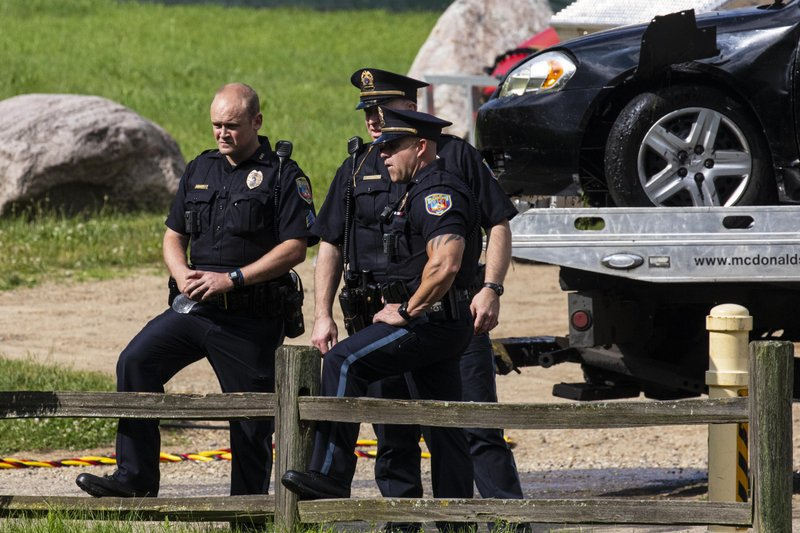 Police remove a black sedan from the Kalamazoo River near Verburg Park, Tuesday, June 18, 2019, after finding the bodies of a mother and child inside the submerged vehicle, in Kalamazoo, Mich. Police believe a second child, who is missing, may also have been inside the vehicle when it entered the water late Monday evening. (Joel Bissell/Kalamazoo Gazette via AP)