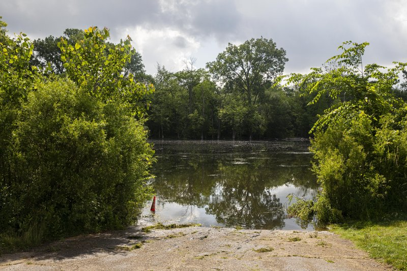 This photo shows the spot on the Kalamazoo River near Verburg Park, Tuesday, June 18, 2019, where police found the bodies of a mother and child inside a submerged vehicle, in Kalamazoo, Mich. Police believe a second child, who is missing, may also have been inside the vehicle when it entered the water late Monday evening. (Joel Bissell/Kalamazoo Gazette via AP)