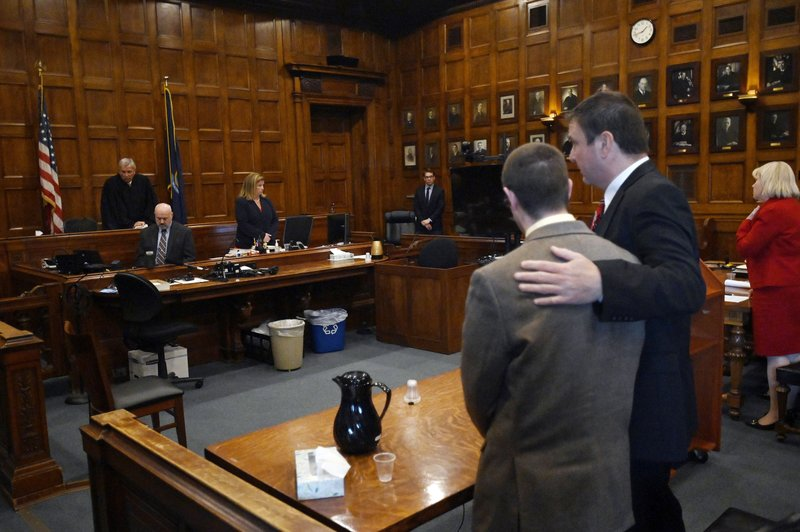 Defense attorney Verne Paradie puts his arm around John D. Williams moments after a jury found him guilty Tuesday, June 18, 2019, in Portland, Maine.  Williams, accused of placing a gun to the neck of a sheriff's deputy and pulling the trigger, was convicted of murder Tuesday after a trial that focused on his state of mind. (Shawn Patrick Ouellette/Portland Press Herald via AP, Pool)
