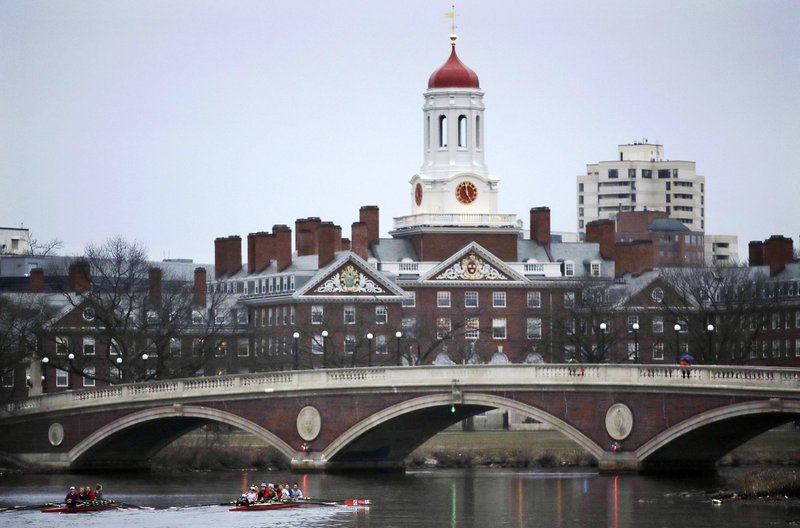 FILE - In this March 7, 2017, file photo, rowers paddle along the Charles River past the Harvard University campus in Cambridge, Mass. The Ivy League university announced Monday, June 17, 2019, that it would revoke an admission offer to a survivor of the Parkland high school massacre because of racist social media posts. The decision serves as a reminder to aspiring college students and all young people that their online comments, even those considered private, can resurface and be used against them. (AP Photo/Charles Krupa, File)
