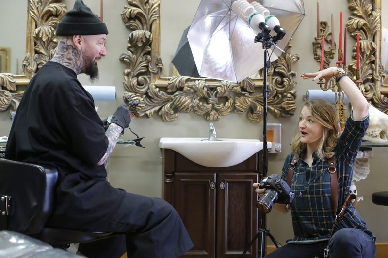 In this Thursday, April 11, 2019 photo Berkshire Eagle photographer Stephanie Zollshan, right, speaks with tattoo artist Brian Brown, of Dalton, Mass., left, at his tattoo parlor, in Dalton. Zollshan photographed Brown for a Berkshire Eagle section called Berkshire Landscapes. The paper now features a new 12-page lifestyle section for Sunday editions, a reconstituted editorial board, a new monthly magazine, and the newspaper print edition is wider. That level of expansion is stunning in an era where U.S. newspaper newsroom employment has shrunk by nearly half over the past 15 years. (AP Photo/Steven Senne)