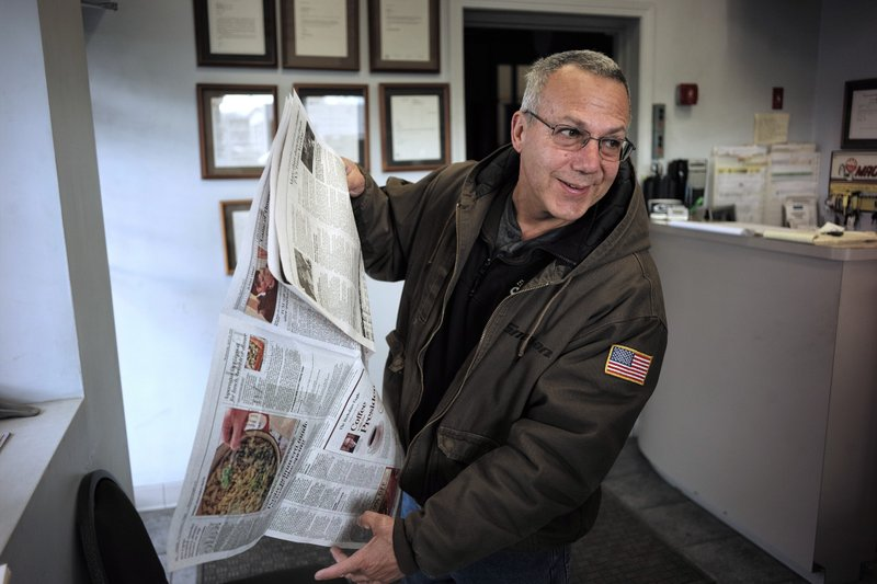In this Wednesday, April 10, 2019 photo Phil Viscuso, owner of East Street Auto Sales, flips through a copy The Berkshire Eagle Newspaper at his shop in Pittsfield, Mass. Viscuso said he has two subscriptions of the print edition of The Berkshire Eagle newspaper so his customers can read the paper while waiting for their cars. (AP Photo/Steven Senne)