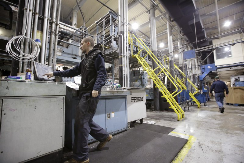 In this Thursday, April 11, 2019 photo pressman Lukus Ladeinde, of Pittsfield, Mass., left, works on the printing presses at The Berkshire Eagle newspaper, in Pittsfield. The paper now features a new 12-page lifestyle section for Sunday editions, a reconstituted editorial board, a new monthly magazine, and the newspaper print edition is wider. That level of expansion is stunning in an era where U.S. newspaper newsroom employment has shrunk by nearly half over the past 15 years. (AP Photo/Steven Senne)