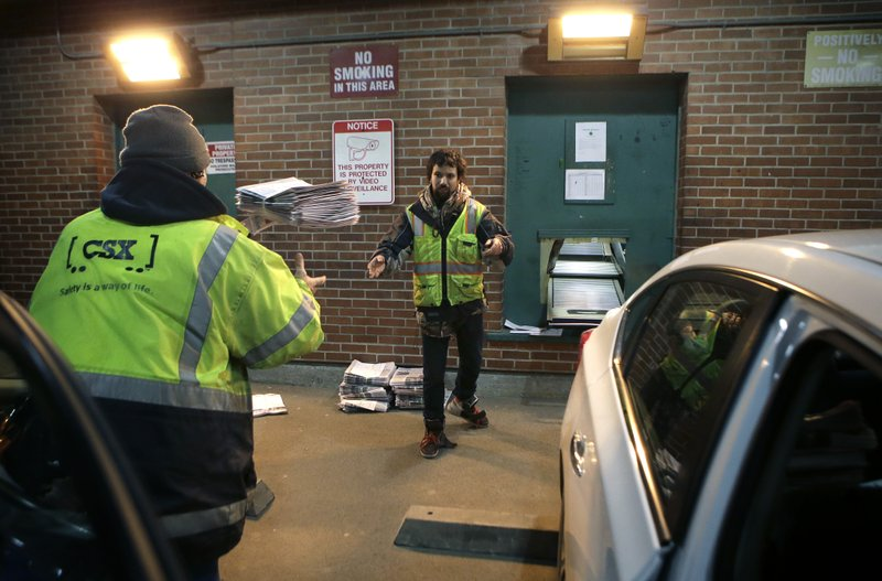 In this Thursday, April 11, 2019 photo worker Zach Charbonneau, of Pittsfield, Mass., throws papers to a colleague while loading vehicles with bundles of papers at The Berkshire Eagle newspaper, in Pittsfield. The paper now features a new 12-page lifestyle section for Sunday editions, a reconstituted editorial board, a new monthly magazine, and the newspaper print edition is wider. That level of expansion is stunning in an era where U.S. newspaper newsroom employment has shrunk by nearly half over the past 15 years. (AP Photo/Steven Senne)