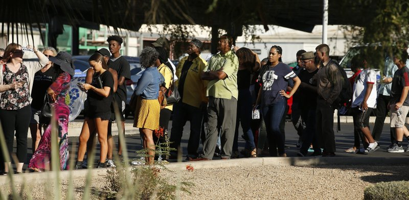 People line up to attend a community meeting, Tuesday, June 18, 2019, in Phoenix. The community meeting stems from reaction to a videotaped encounter that surfaced recently of Dravon Ames and his pregnant fiancee, Iesha Harper, having had guns aimed at them by Phoenix police during a response to a shoplifting report, as well as the issue of recent police-involved shootings in the community. (AP Photo/Ross D. Franklin)