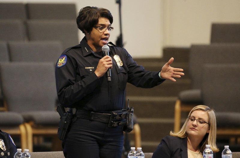Phoenix Police Chief Jeri Williams speaks at a community meeting, as Phoenix Mayor Kate Gallego, seated, listens, Tuesday, June 18, 2019, in Phoenix. The community meeting stems from reaction to a videotaped encounter that surfaced recently of Dravon Ames and his pregnant fiancee, Iesha Harper, having had guns aimed at them by Phoenix police during a response to a shoplifting report, as well as the issue of recent police-involved shootings in the community. (AP Photo/Ross D. Franklin)