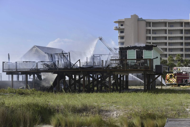Firefighters spray water on a fire that destroyed multiple condominium near the beach at Period Beach, Fla., Wednesday, June 19, 2019. Escambia County officials say the blaze broke out early Wednesday at a development within yards of the Flora-Bama bar and spread quickly. One resident and one firefighter were taken to the hospital with heat-related injuries. (Tony Giberson/Pensacola News Journal via AP)