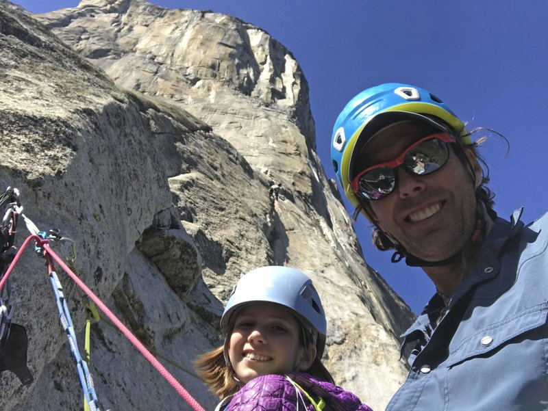 In this June 8, 2019, photo, is Michael Schneiter posing with his daughter, Selah Schneiter, at the beginning of her climb up El Capitan in Yosemite National Park, Calif. A 10-year-old Colorado girl has scaled Yosemite National Park's El Capitan, taking five days to reach the top of the iconic rock formation. Selah Schneiter of Glenwood Springs completed the challenging 3,000-foot (910 meters) climb last week with the help of her father and a family friend. (Michael Schneiter via AP)