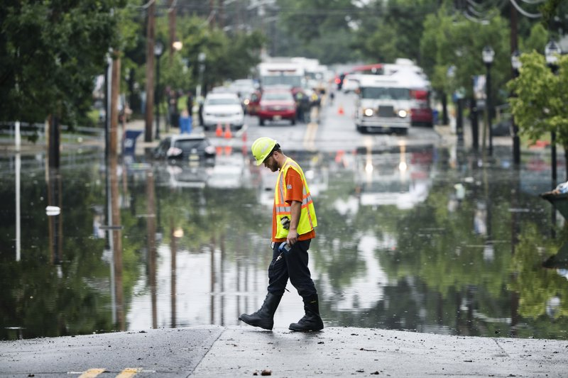 A utility worker walks the edge of the floodwaters submerging Broadway in Westville, N.J. Thursday, June 20, 2019. Severe storms containing heavy rains and strong winds spurred flooding across southern New Jersey, disrupting travel and damaging some property. (AP Photo/Matt Rourke)