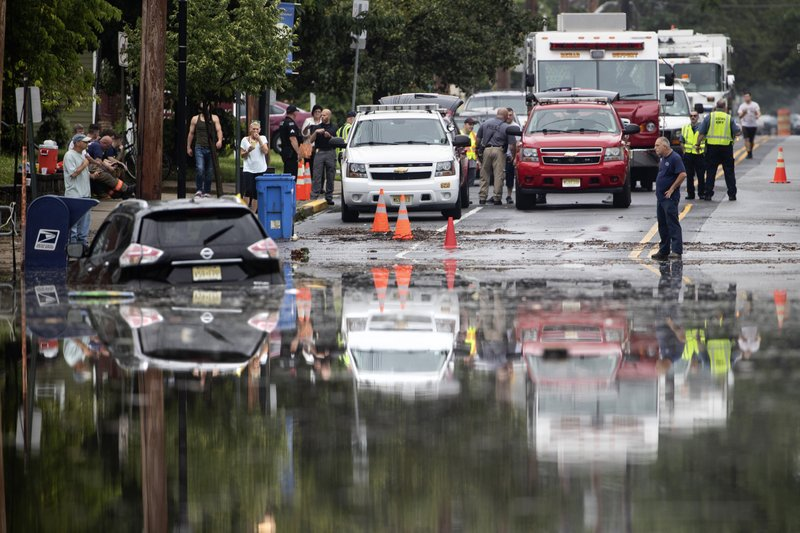 Officials and residents gather on the edge of the floodwaters submerging Broadway in Westville, N.J. Thursday, June 20, 2019. Severe storms containing heavy rains and strong winds spurred flooding across southern New Jersey, disrupting travel and damaging some property. (AP Photo/Matt Rourke)