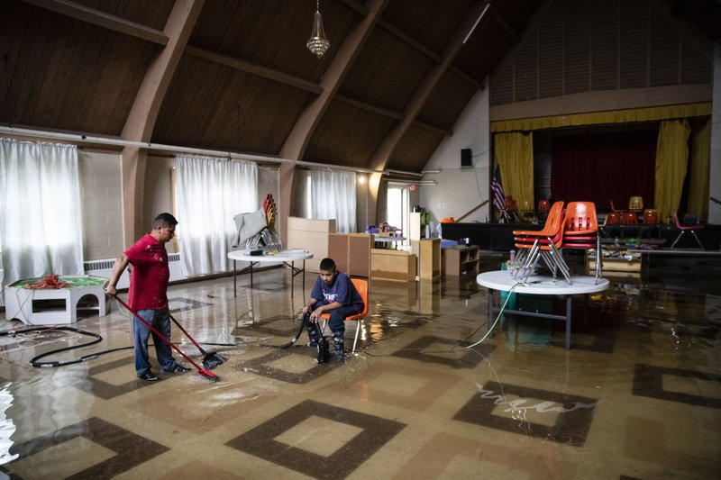 Parishioners pump out floodwater inside the Macedonia Baptist Church in Westville, N.J. Thursday, June 20, 2019. Severe storms containing heavy rains and strong winds spurred flooding across southern New Jersey, disrupting travel and damaging some property. (AP Photo/Matt Rourke)