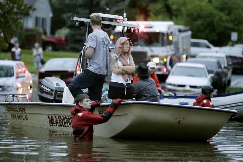 Rescuers guide boats on High St as they bring people to safety after overnight thunderstorms flooded much of Westville, N.J. on Wednesday, June 20, 2019. ( Elizabeth Robertson/The Philadelphia Inquirer via AP)
