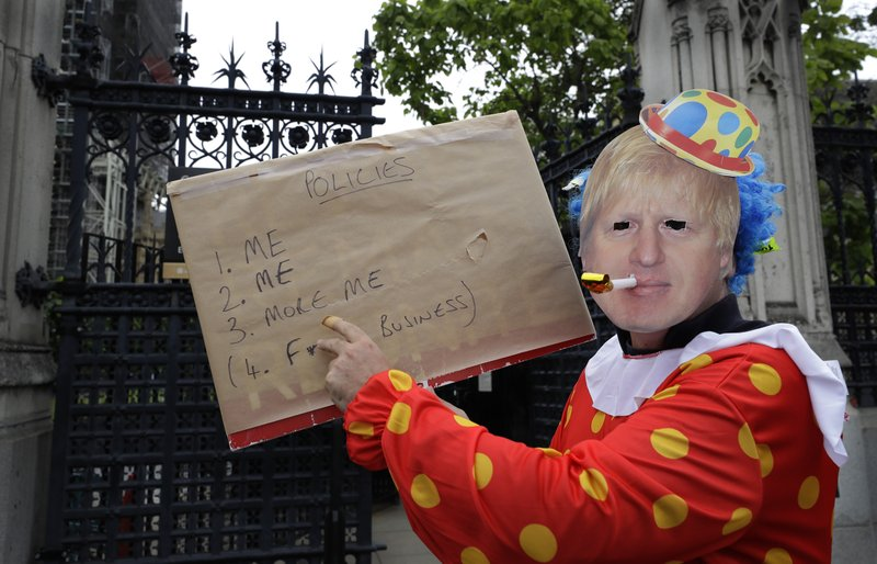 A demonstrator in a Boris Johnson mask poses with a banner outside the Houses of Parliament in London, Thursday, June 20, 2019. The contest to become Britain's next prime minister is down to its final three candidates, with Environment Secretary Michael Gove and Foreign Secretary Jeremy Hunt chasing front-runner Boris Johnson for a spot in a deciding runoff. (AP Photo/Kirsty Wigglesworth)