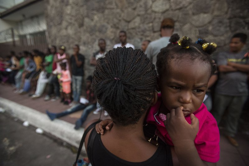 A Haitian woman carries her daughter as she waits outside the Mexican Commission for Migrant Assistance office, to get the documents needed that allow them to stay in Mexico, in Tapachula, early Thursday, June 20, 2019. The flow of migrants into southern Mexico has seemed to slow in recent days as more soldiers, marines, federal police, many as part of Mexico's newly formed National Guard, deploy to the border under a tougher new policy adopted at a time of increased pressure from the Trump administration.  (AP Photo/Oliver de Ros)