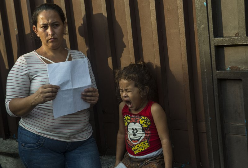 Ana Isabel, and her daughter, Breidi, wait in line outside the Mexican Commission for Migrant Assistance office to get the documents needed that allows them to stay in Mexico, in Tapachula, early Thursday, June 20, 2019. The flow of migrants into southern Mexico has seemed to slow in recent days as more soldiers, marines, federal police, many as part of Mexico's newly formed National Guard, deploy to the border under a tougher new policy adopted at a time of increased pressure from the Trump administration.  (AP Photo/Oliver de Ros)