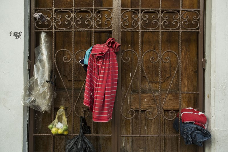 Clothes belonging to migrants hang in a door next to the Mexican Commission for Migrant Assistance office where migrants wait to get the documents needed that allows them to stay in Mexico, in Tapachula, Thursday, June 20, 2019. The flow of migrants into southern Mexico has seemed to slow in recent days as more soldiers, marines, federal police, many as part of Mexico's newly formed National Guard, deploy to the border under a tougher new policy adopted at a time of increased pressure from the Trump administration.  (AP Photo/Oliver de Ros)