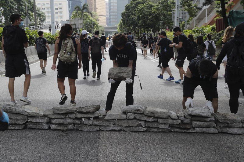 Protesters use stones to block a road in Hong Kong on Friday, June 21, 2019. Several hundred mainly student protesters gathered outside Hong Kong government offices Friday morning, with some blocking traffic on a major thoroughfare, after a deadline passed for meeting their demands related to controversial extradition legislation that many see as eroding the territory's judicial independence. (AP Photo/Kin Cheung)