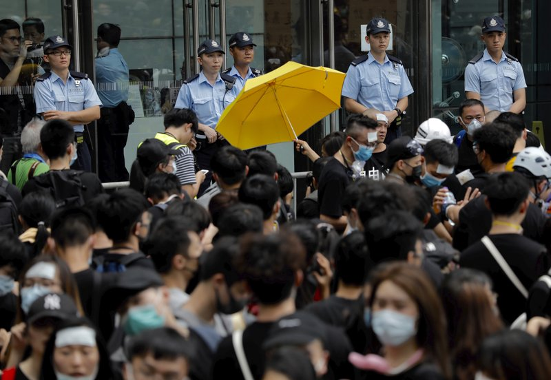 A protester holds out a yellow umbrella towards a line of police officers in Hong Kong Friday, June 21, 2019. Several hundred mainly student protesters gathered outside Hong Kong government offices Friday morning, with some blocking traffic on a major thoroughfare, after a deadline passed for meeting their demands related to controversial extradition legislation that many see as eroding the territory's judicial independence. (AP Photo/Vincent Yu)