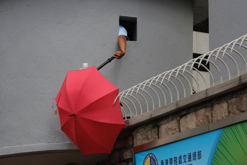 A police officer tries to remove an umbrella blocking the view of security cameras outside the police headquarters in Hong Kong Friday, June 21, 2019. Several hundred mainly student protesters gathered outside Hong Kong government offices Friday morning, with some blocking traffic on a major thoroughfare, after a deadline passed for meeting their demands related to controversial extradition legislation that many see as eroding the territory's judicial independence. (AP Photo/Kin Cheung)