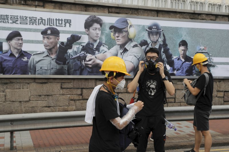 Protesters prepare protection gears as they gather near a poster with the words