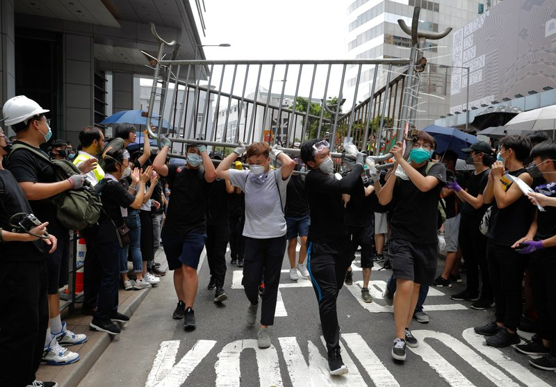Protesters carry barricades to surround the police headquarters in Hong Kong on Friday, June 21, 2019. Several hundred mainly student protesters gathered outside Hong Kong government offices Friday morning, with some blocking traffic on a major thoroughfare, after a deadline passed for meeting their demands related to controversial extradition legislation that many see as eroding the territory's judicial independence. (AP Photo/Vincent Yu)