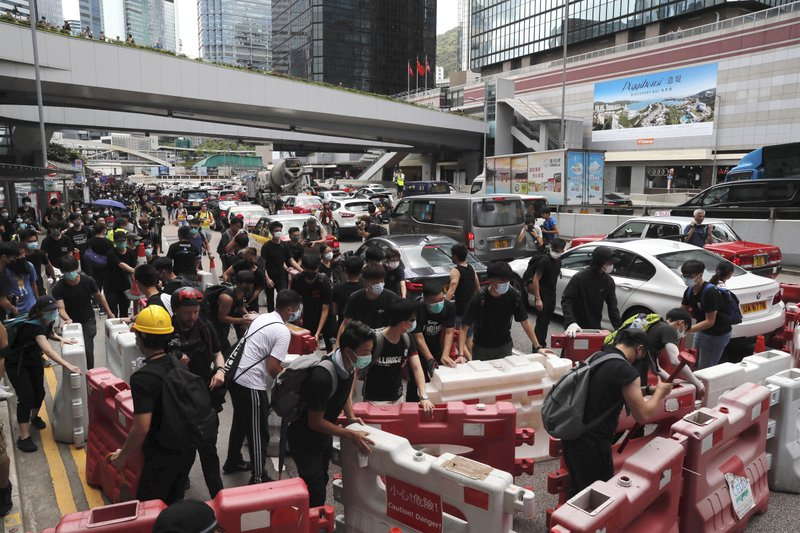 Protesters use barricades to surround the police headquarters in Hong Kong on Friday, June 21, 2019. Several hundred mainly student protesters gathered outside Hong Kong government offices Friday morning, with some blocking traffic on a major thoroughfare, after a deadline passed for meeting their demands related to controversial extradition legislation that many see as eroding the territory's judicial independence. (AP Photo/Kin Cheung)