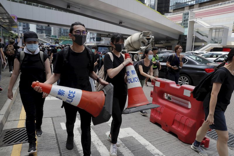 Protesters carry police cones and barricade to surround the police headquarters in Hong Kong on Friday, June 21, 2019. Several hundred mainly student protesters gathered outside Hong Kong government offices Friday morning, with some blocking traffic on a major thoroughfare, after a deadline passed for meeting their demands related to controversial extradition legislation that many see as eroding the territory's judicial independence. (AP Photo/Kin Cheung)