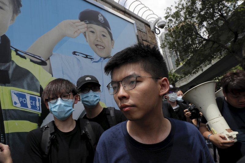 Pro-democracy activist Joshua Wong, foreground, joins other protesters to surround the police headquarters in Hong Kong on Friday, June 21, 2019. Several hundred mainly student protesters gathered outside Hong Kong government offices Friday morning, with some blocking traffic on a major thoroughfare, after a deadline passed for meeting their demands related to controversial extradition legislation that many see as eroding the territory's judicial independence. (AP Photo/Kin Cheung)