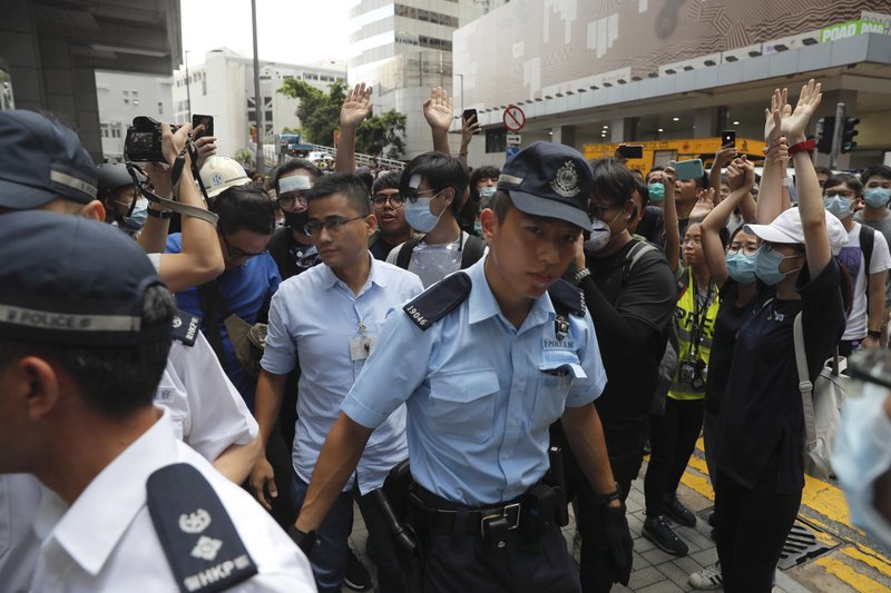 A police officer passes by protesters surrounding the police headquarters in Hong Kong on Friday, June 21, 2019. Several hundred mainly student protesters gathered outside Hong Kong government offices Friday morning, with some blocking traffic on a major thoroughfare, after a deadline passed for meeting their demands related to controversial extradition legislation that many see as eroding the territory's judicial independence. (AP Photo/Kin Cheung)