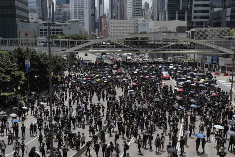 Protesters march to surround the police headquarters in Hong Kong on Friday, June 21, 2019. Several hundred mainly student protesters gathered outside Hong Kong government offices Friday morning, with some blocking traffic on a major thoroughfare, after a deadline passed for meeting their demands related to controversial extradition legislation that many see as eroding the territory's judicial independence. (AP Photo/Kin Cheung)