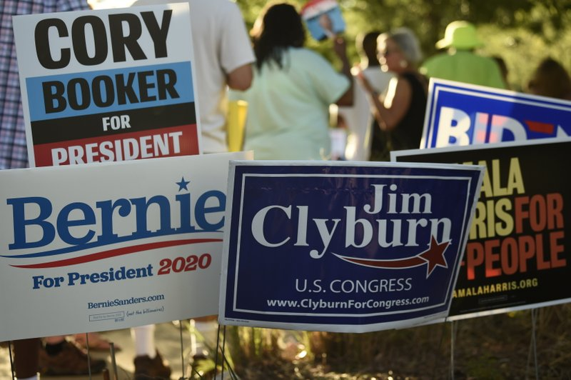 Supporters of many of the Democrats seeking their party's presidential nomination plant signs outside the venue for Majority Whip Jim Clyburn's