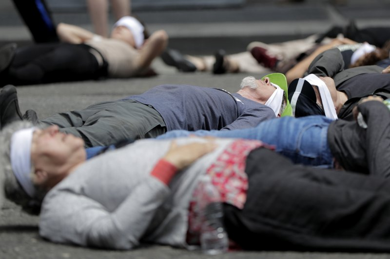 Activists lie in the middle of 8th Avenue in front of the New York Times building during a climate change rally, Saturday, June 22, 2019, in New York. Activists were taking into custody after blocking traffic during a sit-in to demand coverage of climate change by the newspaper. (AP Photo/Julio Cortez)