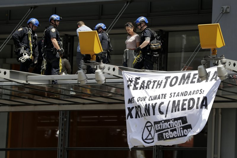 New York Police officers take into custody activists who climbed on the awning of the New York Times building to hang signs during a climate change rally, Saturday, June 22, 2019, in New York. Activists blocked traffic along 8th Avenue during a sit-in to demand coverage of climate change by the newspaper. (AP Photo/Julio Cortez)