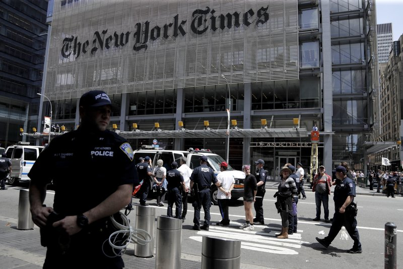 New York Police officers take into custody activists during a climate change rally outside of the New York Times building, Saturday, June 22, 2019, in New York. Activists blocked traffic along 8th Avenue during a sit-in to demand coverage of climate change by the newspaper. (AP Photo/Julio Cortez)