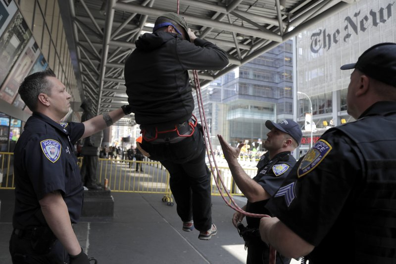 New York Police officers wait for a man to finish rappelling down the side of the Port Authority Building to take him into custody during a climate change rally outside of the New York Times building, Saturday, June 22, 2019, in New York. Activists blocked traffic along 8th Avenue during a sit-in to demand coverage of climate change by the newspaper. (AP Photo/Julio Cortez)