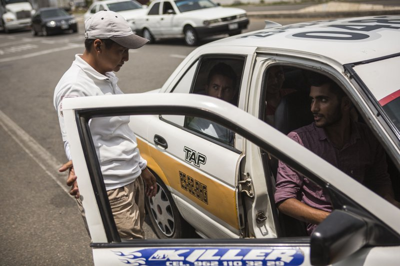 An officer from the National Migration Institute stops a taxi carrying migrants from Bangladesh, at an immigration checkpoint known as Viva Mexico, near Tapachula, Mexico, Friday, June 21, 2019. Mexico's foreign minister says that the country has completed its deployment of some 6,000 National Guard members to help control the flow of Central American migrants headed toward the U.S. (AP Photo/Oliver de Ros)