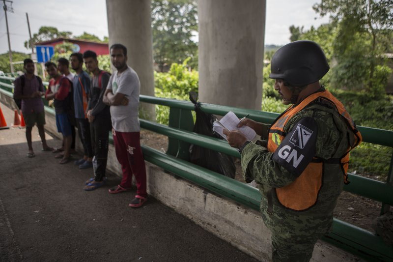 A Mexican National Guardsman stops a group of migrants from Bangladesh, India and Pakistan, at an immigration checkpoint known as Viva Mexico, near Tapachula, Mexico, Friday, June 21, 2019. Mexico's foreign minister says that the country has completed its deployment of some 6,000 National Guard members to help control the flow of Central American migrants headed toward the U.S. (AP Photo/Oliver de Ros)