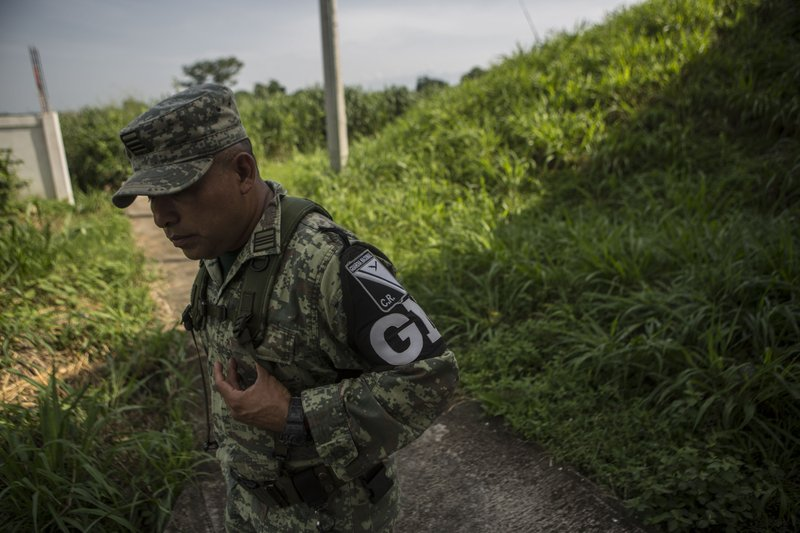 Military police wearing the insignia of the new National Guard provide perimeter security while a migration agent waits to check documents of passengers in passing transport, at an immigration checkpoint in El Manguito, south of Tapachula, Mexico, Friday, June 21, 2019. Mexico's foreign minister says that the country has completed its deployment of some 6,000 National Guard members to help control the flow of Central American migrants headed toward the U.S. (AP Photo/Oliver de Ros)