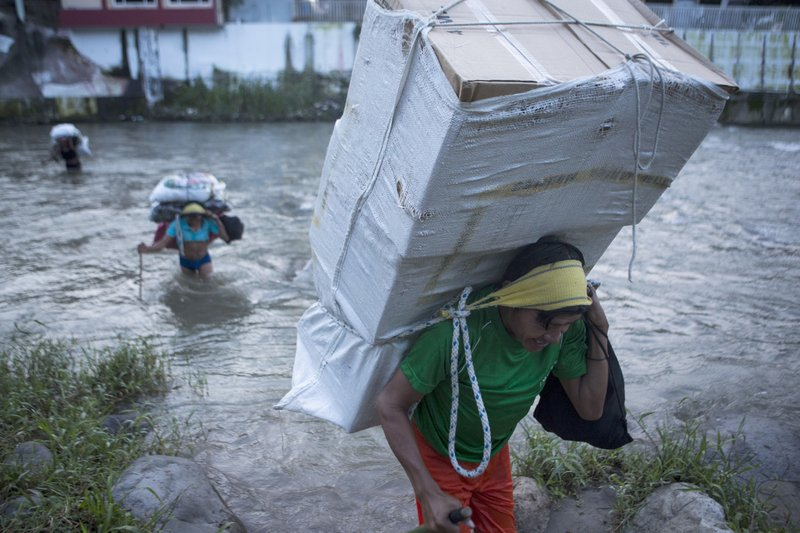 Men carry loads of supplies as they cross the Suchiate river from Guatemala into Talisman, Mexico, Friday, June 21, 2019. Mexico's foreign minister says that the country has completed its deployment of some 6,000 National Guard members to help control the flow of Central American migrants headed toward the U.S.(AP Photo/Oliver de Ros)