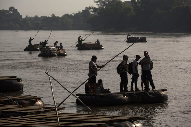 Rafts carry passengers and supplies across the Suchiate River between Tecun Uman, Guatemala, and Ciudad Hidalgo, Mexico, Friday, June 21, 2019. Mexico's foreign minister says that the country has completed its deployment of some 6,000 National Guard members to help control the flow of Central American migrants headed toward the U.S. (AP Photo/Oliver de Ros)