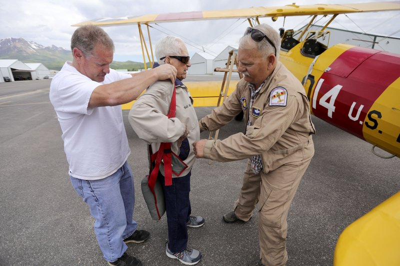 In this June 14, 2019, photo Dane Wilkinson, left, and Doug Compton, right, help retired Air Force Lt. Col. Bill Willis, 97, put on a parachute before a flight at the Morgan County Airport in Morgan, Utah. (Kristin Murphy/The Deseret News via AP)