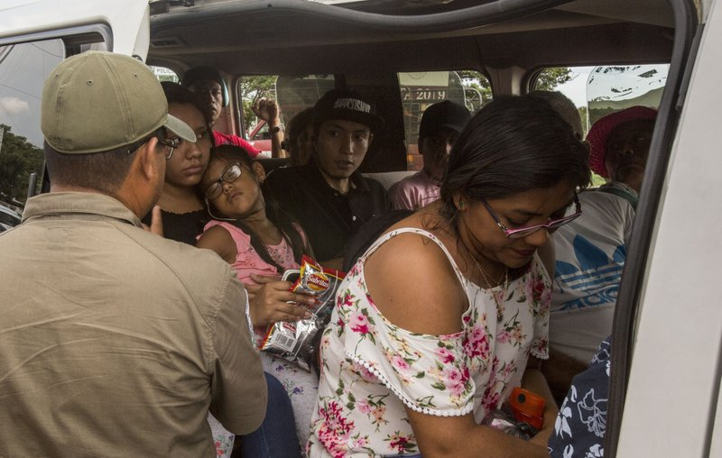 A Mexican migration agent, left, checks passengers' documents at an immigration checkpoint in Arriaga, on Mexico's southern border, Sunday, June 23, 2019. Residents of Arriaga expressed a mixture of concern for the migrants they have grown accustomed to hosting and relief that officials are looking to get a better handle on migrant flows. (AP Photo/Oliver de Ros)