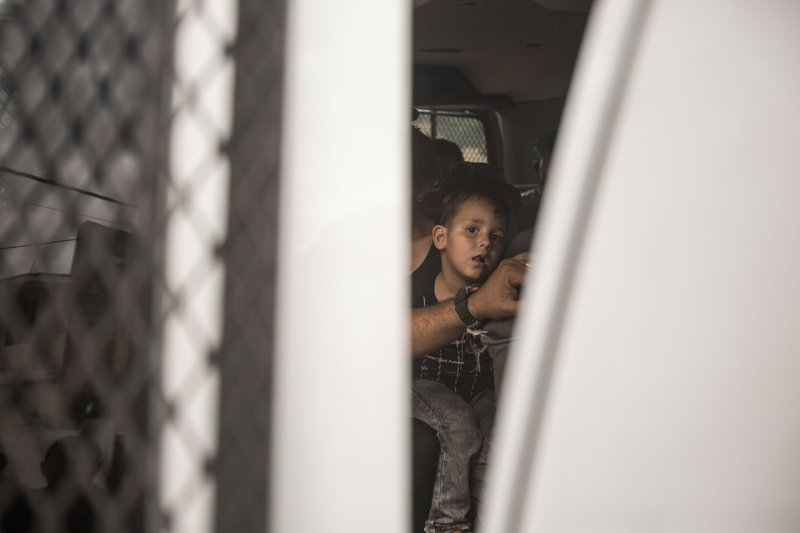 A youth without legal permission to be in Mexico sits inside an immigration van outside an office of the Attorney General as he and other migrants wait to be transported to Tapachula from Arriaga, Mexico, Sunday, June 23, 2019. Mexico has completed its deployment of 6,000 National Guard agents to help control the flow of migrants headed toward the U.S. and filled immigration agency posts to regulate border crossings, the government said Friday. (AP Photo/Oliver de Ros)wld