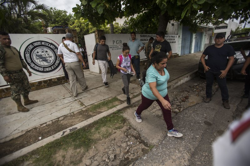 People without legal permission to be in Mexico leave an office of the Attorney General before being sent to Tapachula in an immigration van, as a member of the National Guard, left, stands watch in Arriaga, Mexico, Sunday, June 23, 2019. Mexico has completed its deployment of 6,000 National Guard agents to help control the flow of migrants headed toward the U.S. and filled  immigration agency posts to regulate border crossings, the government said Friday. (AP Photo/Oliver de Ros)