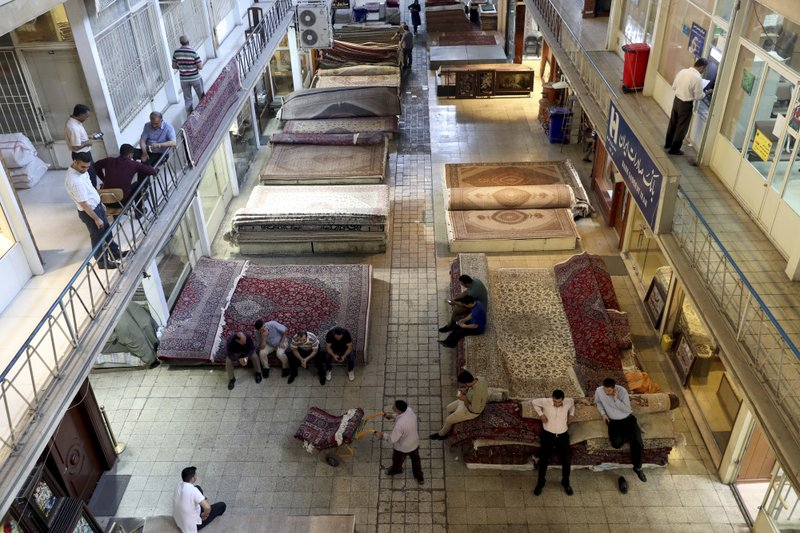 Iranian merchants conduct their business at a carpet market of the old main bazaar in Tehran, Iran, Sunday, June 23, 2019. As the U.S. piles sanction after sanction on Iran, it's the average person who feels it the most. Depreciation and inflation makes everything more expensive. A simple cell phone is about two months' salary for the average government worker, while a single iPhone costs 10-months' salary. (AP Photo/Ebrahim Noroozi)